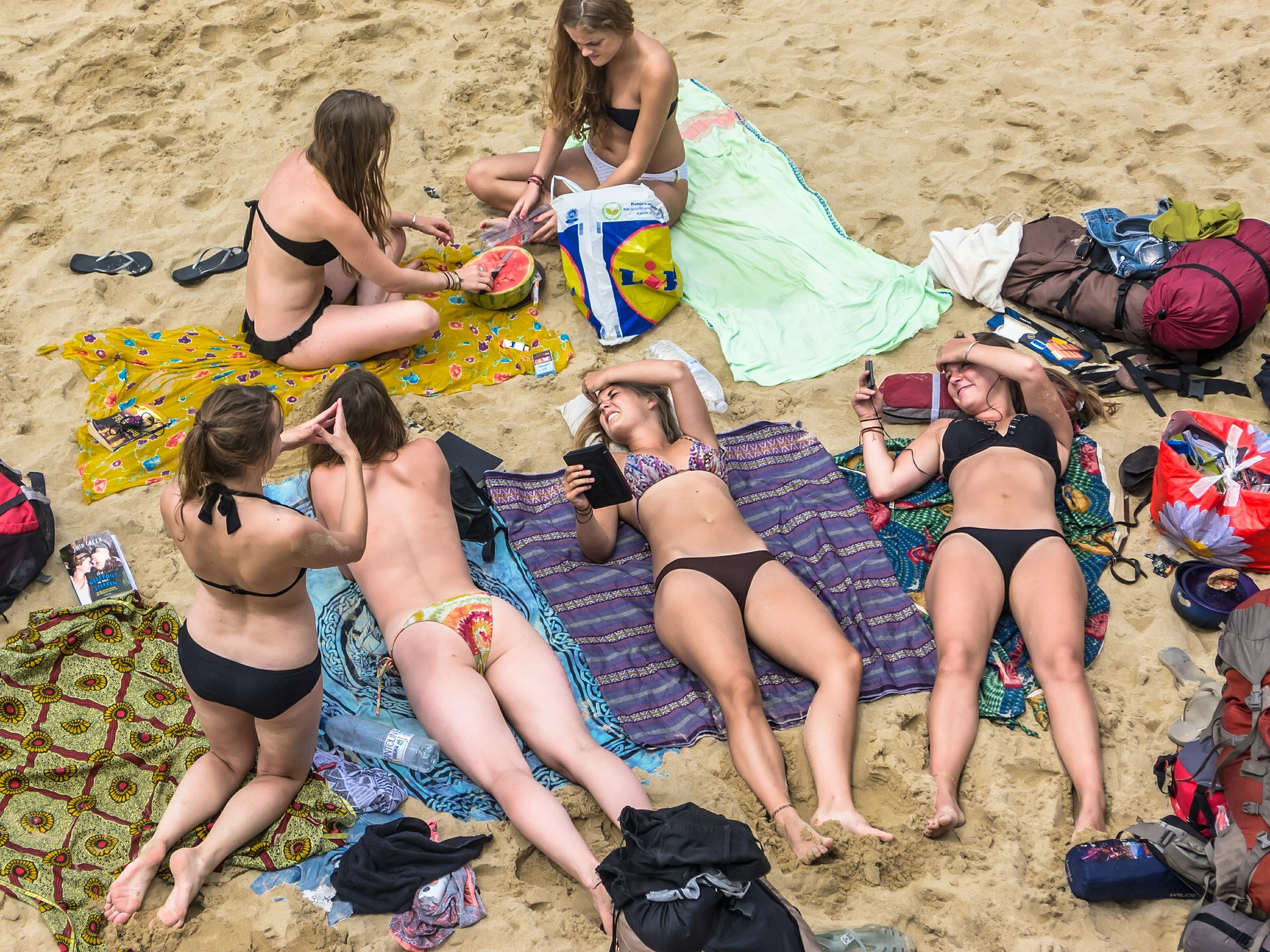 Girls on a beach-day out chatting and sunbathing