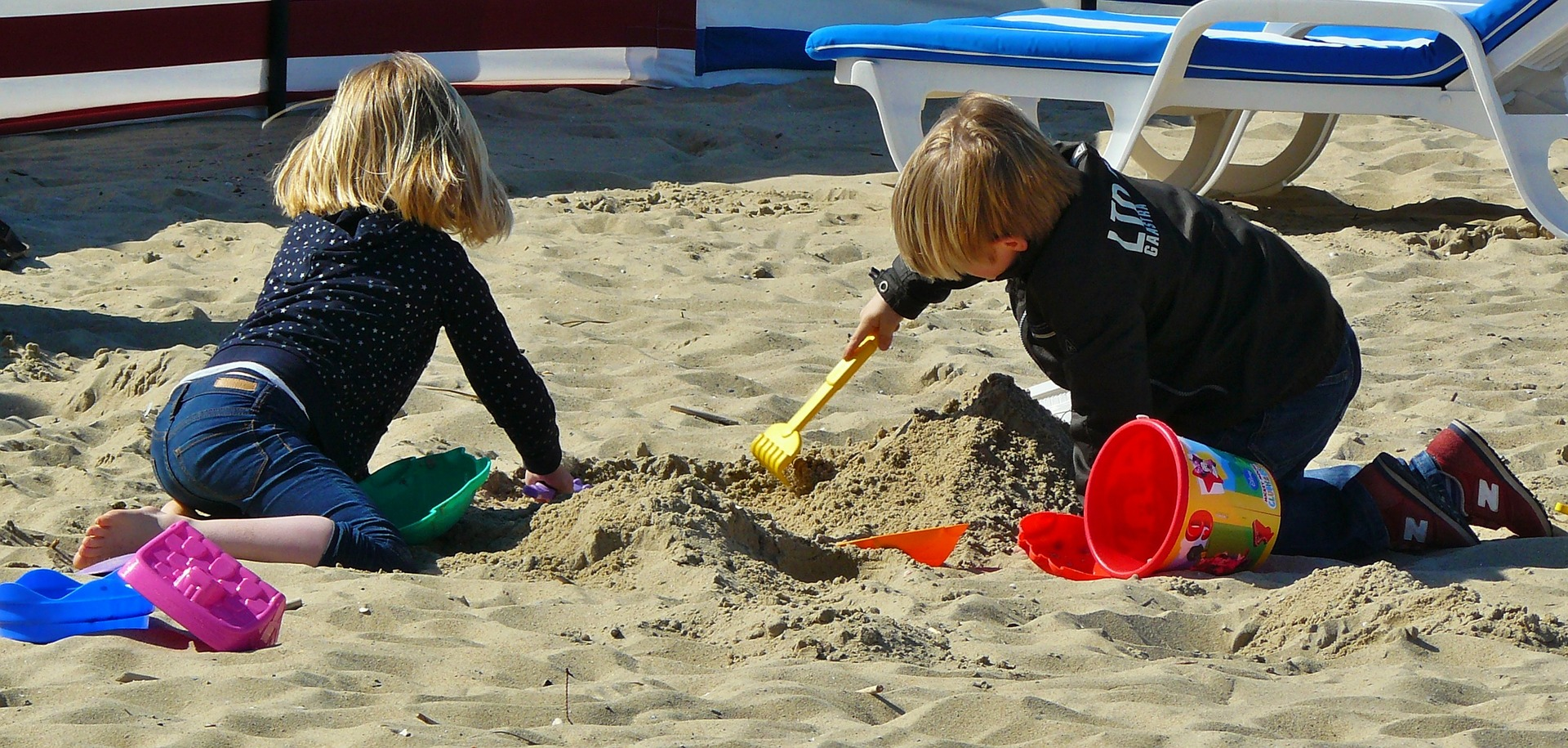Children playing with buckets and spades on a sandy beach